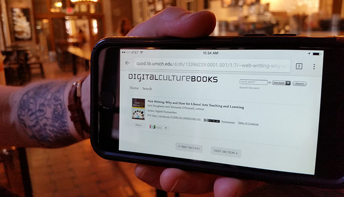 Close-up of a human hand holding a mobile device with the homepage for Digital Culture Books on the screen.