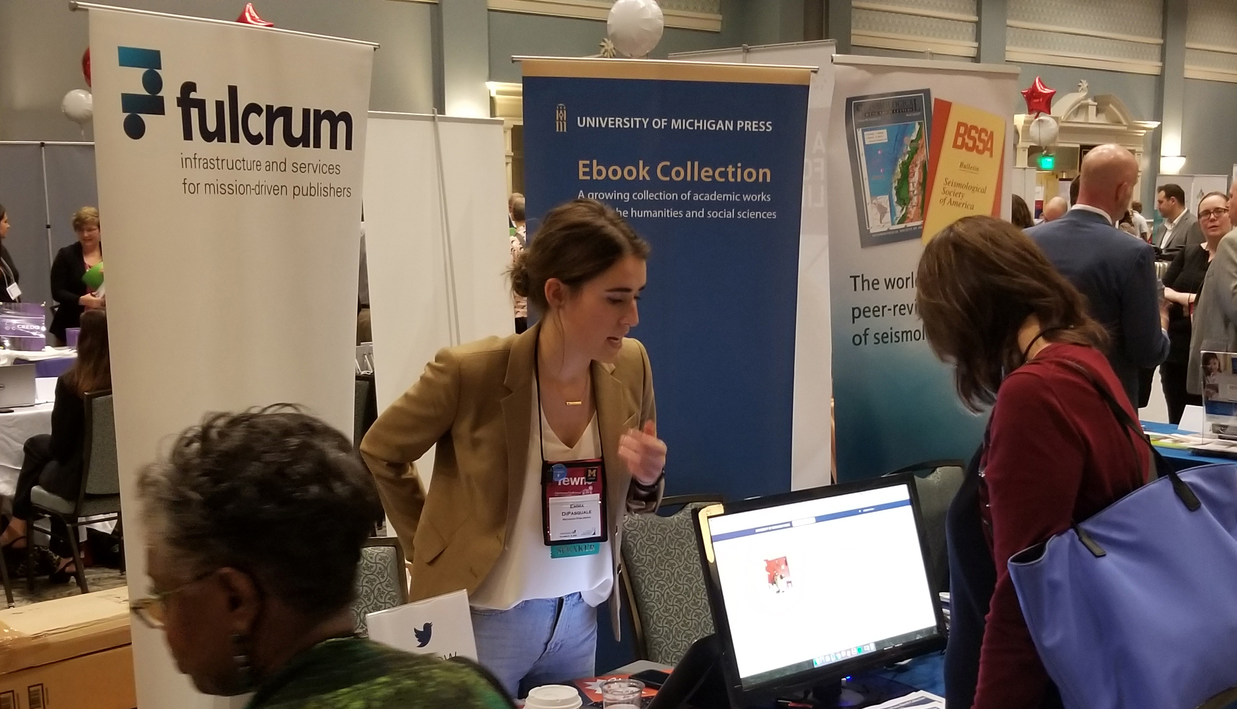 A photograph of a young woman showing a digital ebook from the University of Michigan Press Ebook collection to a Charleston conference attendee at the Michigan Publishing display booth.