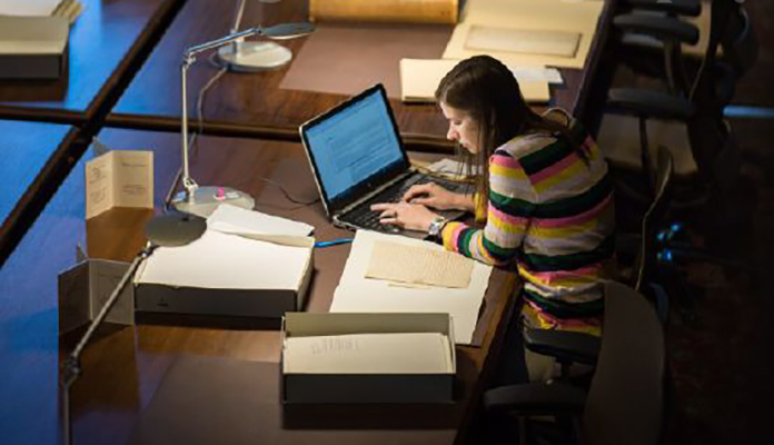 A photograph of a young woman studying with books and a computer at a table in the U-M Law Library.