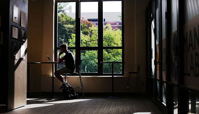 A photograph of a room covered mostly with shadow, where a student with short hair sits at a table in front of a large window with their laptop open. The tops of trees and a nearby building can be seen through the window.